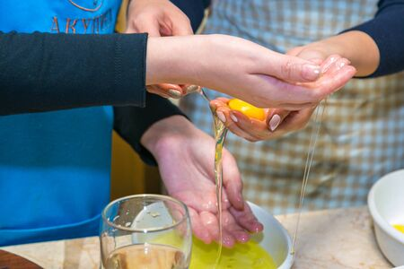separating: Women hands holding separate egg Stock Photo