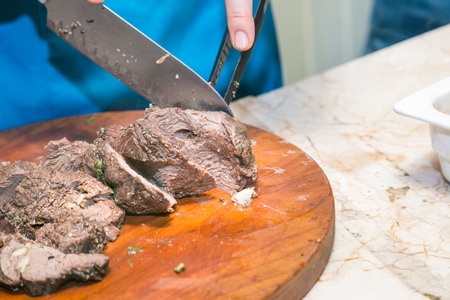 roasting pan: Cook cuts roasted beef meat Stock Photo