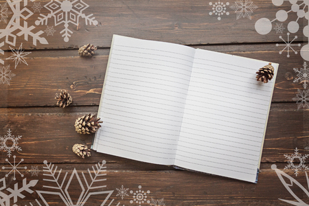 overly: top image of open notebook with blank pages, next to pine cones  over wooden table. top image overly with snowflakes  Flat lay style Stock Photo