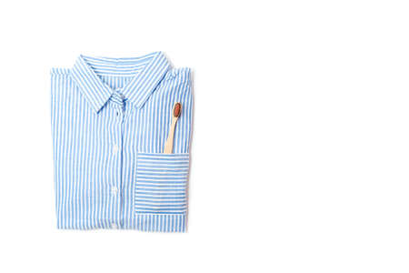 pajamas shirt and wooden toothbrush on a white background