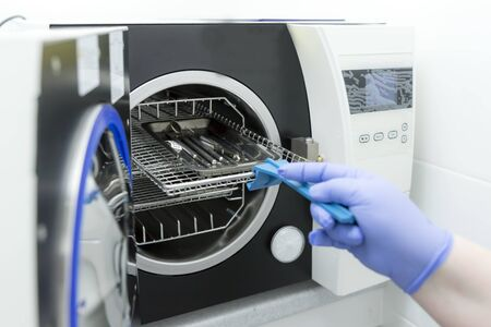 Sterilizing medical instruments in autoclave. Dental office.