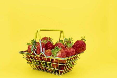 shopping basket with strawberries in a medical mask on a yellow background Stock Photo
