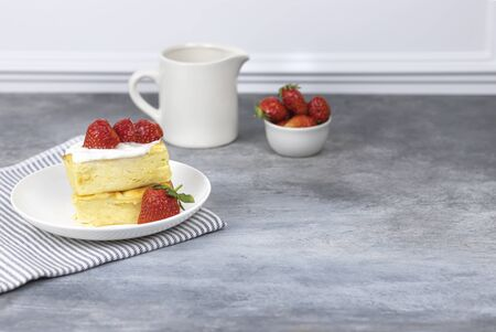 cottage cheese casserole with cream and strawberries on a white plate Stok Fotoğraf