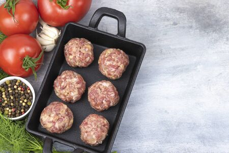 Raw meatballs on the wooden cutting board