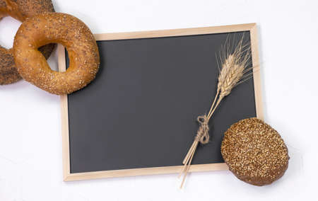 assortment of baked bread on white wooden background and black letter board flat lay. Top view with copy space Stock fotó