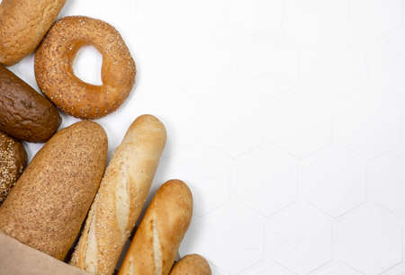 Various kinds of bread on white factual background, bread flay lay