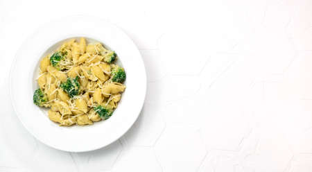 Pasta with green vegetables, broccoli, melted cheese and creamy sauce in white bowl on white table. Top view. Copy space.