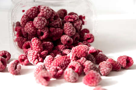 Plastic bag with frozen raspberry on white background with shadows, top view. 스톡 콘텐츠