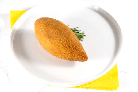 Chicken Kiev cutlet with mashed potatoes and slice on a plate, white background