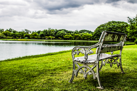 The old white bench on the water.  In the natural garden Stock Photo