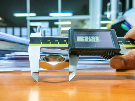 Digital calipers measure the iron on the desk with bright lighting. For quality control in accordance with international standards. Stock Photo