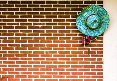 Farmers hat hung beside an old orange brick wall.