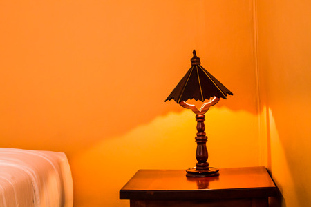 Wooden lamp is placed on the old brown wooden table next to the bed with orange light. Stock fotó