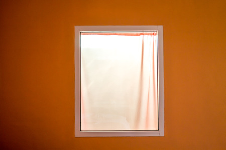 The white window has white curtains next to the orange walls. The light from the electricity shines through.