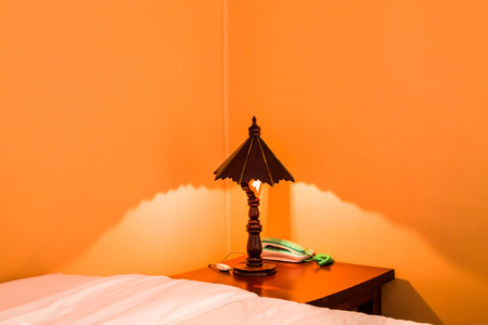 The wooden lamp is placed on an old brown wooden desk next to a green phone. By the bed