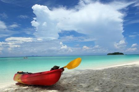 Colourful kayaks on tropical beach photo