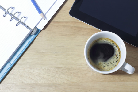 Office table with notepad  and coffee cup. View from above with copy space
