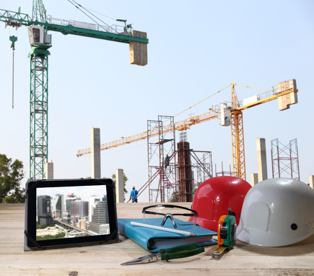 file of safety helmet and safety glasses on wood table in front of building construction background