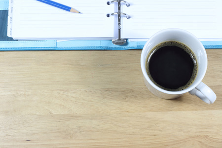 office space: Office table with notepad  and coffee cup. View from above with copy space