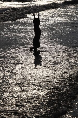 Silhouette of child on the beach, holding his hands up, hugging the sun photo