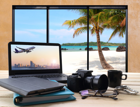 beach window: working table and window seat over looking the sea and beach with perspective view of jet airliner in flight from screen computer Stock Photo