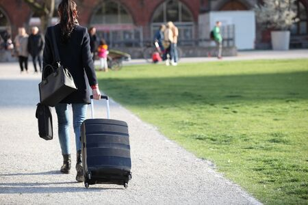 Beautiful woman with suitcases crossing the street in a big city.Beautiful woman  on a street and holding a suitcase. young woman with long legs in a urban setting Stockfoto