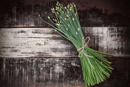 cebollines: floración cebollino ajo chino en mesa de madera Foto de archivo