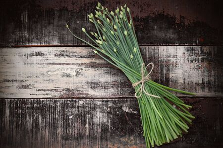 chives: flowering chinese garlic chives on wooden table Stock Photo