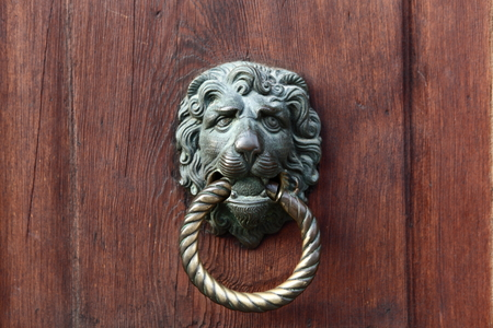 furniture part: Door knocker in the shape of a lion on old wood door Stock Photo