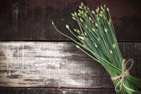 cebolleta: floración cebollino ajo chino en mesa de madera Foto de archivo