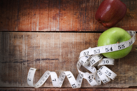 Green apple core and measuring tape. Diet concept with copy space on wood background