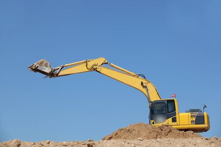 earth moving equipment: excavator in action  on site