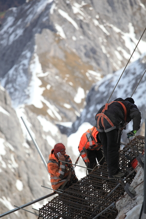 evacuate: GARMISCH PARTENKIRCHEN , GERMANY  ,  April 16 , 2015  Mountain working team members in dangerous area ,they are working look like rescue as they evacuate an injured climber from a rock pinnacle.