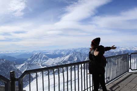 zugspitze mountain: Winter snow covered mountain Zugspitze in Germany Europe. woman  standing and happy at moment time