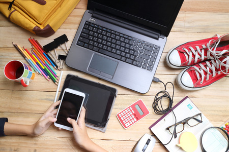 Close up hands holding big smart phone while connecting to wireless, businessman using technology sitting at modern loft wooden desk, people and modern devices everywhere