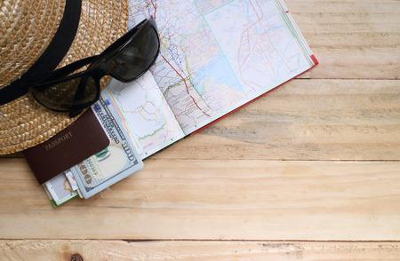 Pojęcie podróży, Przygotowanie do podróży, pieniądze, paszport, mapa drogowa na drewnianym stole