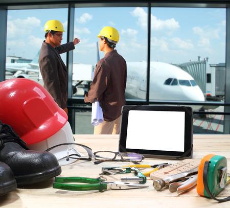 the maintenance: dos mecánicos de aire, ingenieros, con un gran avión de pasajeros en el fondo, las actividades de tierra del aeropuerto