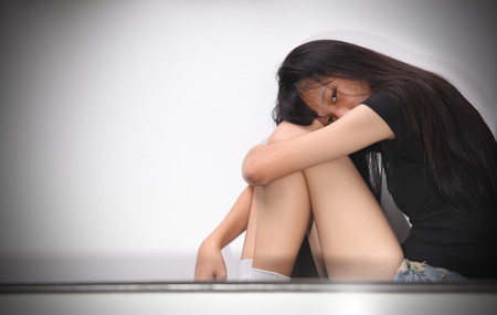 major depression: Sad woman or girl  with depression sitting on the floor Stock Photo