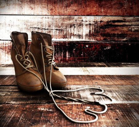 military boots: Old and dirty military boots isolated on wood background Stock Photo