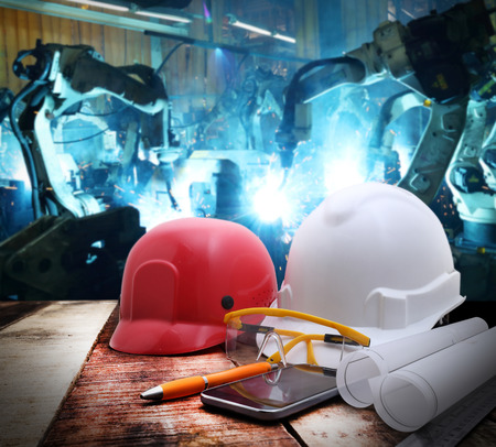 file of safety helmet and drawing  on wood table with group robot welding automotive industrail background