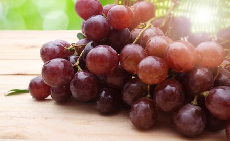 Bunch of red grapes on wooden table Stockfoto