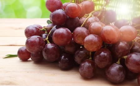 uvas: Racimo de uvas rojas en mesa de madera Foto de archivo