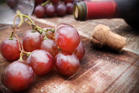 vins: Red wine and grapes in vintage setting