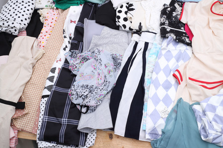reusing: display of second hand clothes on floor,donation,reusing or reselling for second life sold at garage sale for fashion fans or economic shopping