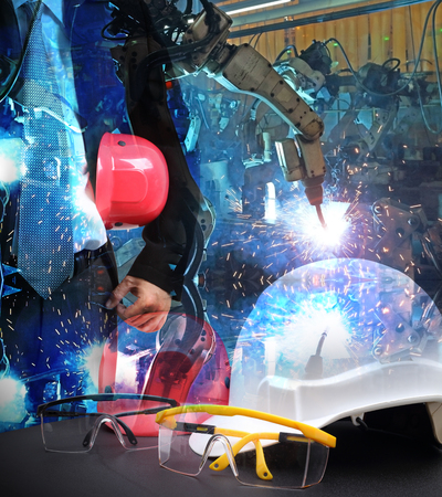 construction machinery: Double exposure file of safety helmet  on working table with group welding robots are working In the automotive parts industry background Stock Photo