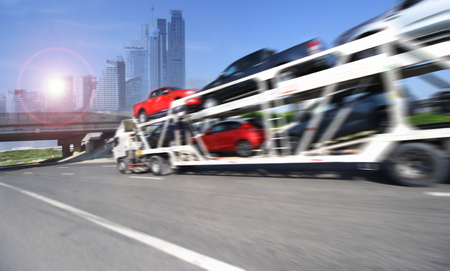 car carrier: The trailer transports cars on highway with big city background