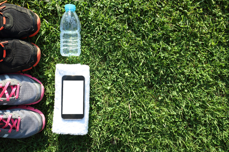 sports activities: Sport shoes and water with set for sports activities on  on green grass with copy space Stock Photo