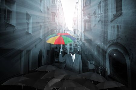 dark city: Be a different businessman concept , man holding rainbow umbrella in mass of black umbrellas with dark city  background
