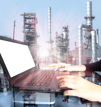 industries: Business woman hand working on  laptop computer with oil refinery industry in metallic color style use as metal style of heavy industry background