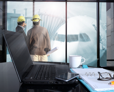 plane table: Office workplace with laptop and smart phone on table and  blurred background of Cabin of plane in air port